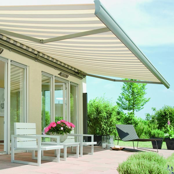 an awning extended over some garden furniture, with garden in the background