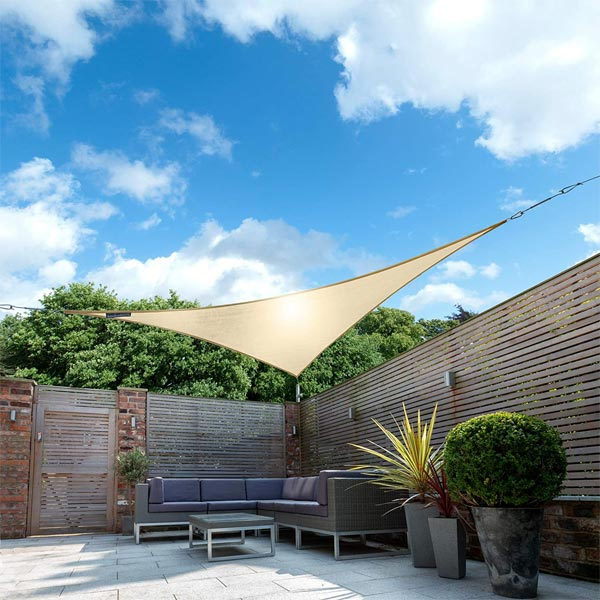 an ivory shade sail installed on some fencing in the corner of a garden